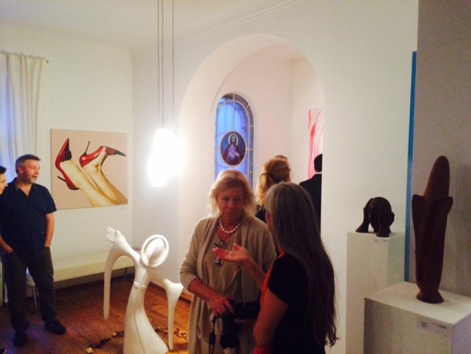 Ausstellungs-Besucher hinter Skulptur Daemonis